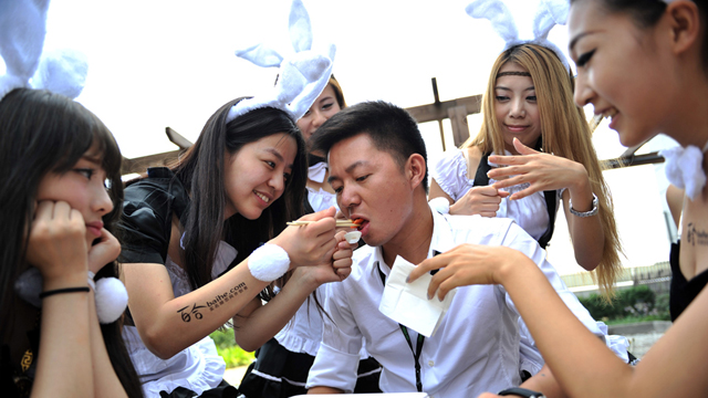 """7月28日,一群身着女仆装头戴兔耳的性感女郎来到北京一IT公司内,为这里工作的单身男性献上""""七夕福利""""。女郎们不仅为""""挨踢族""""(IT族)喂送早餐、递送文件、端茶倒水,还为男士们送上特制的棉花糖""""胸器""""蛋糕。图为女仆与""""挨踢男""""共进午餐。"""